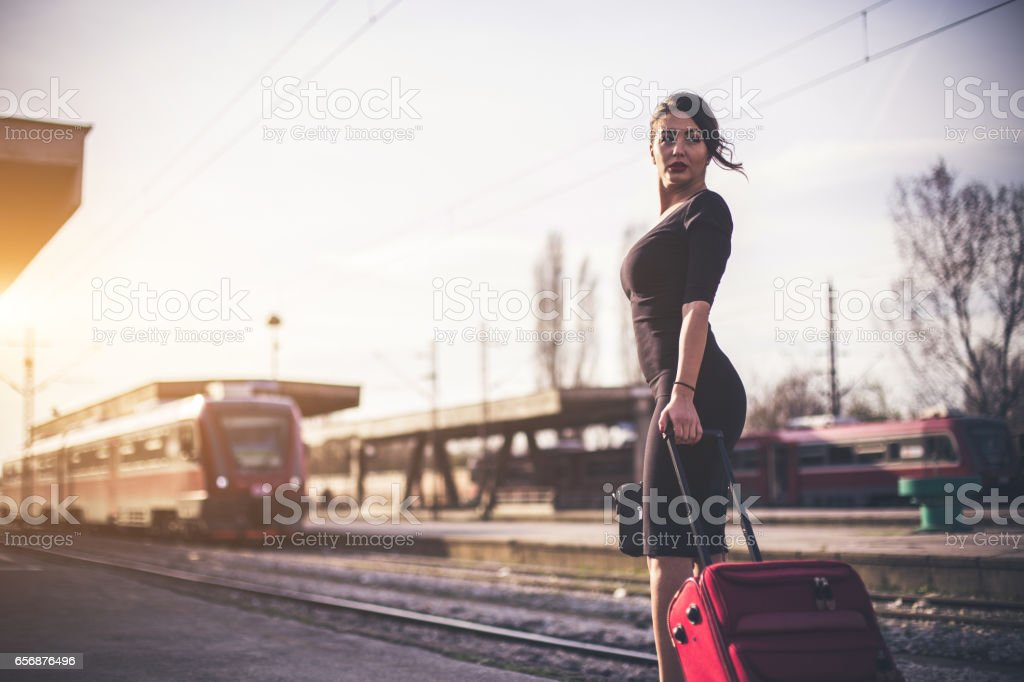 Sensual woman pulling the luggage at the train station stock photo