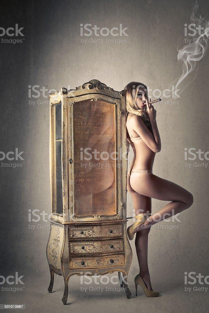 Sensual woman smoking a cigar stock photo