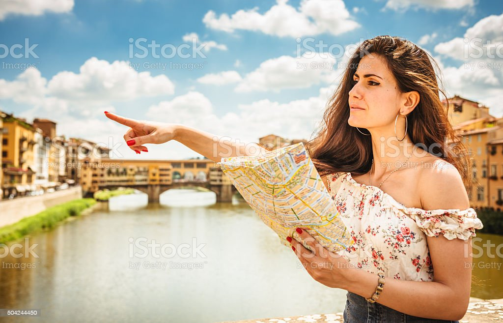 sensual woman standing in Florence pointing at the bridge stock photo