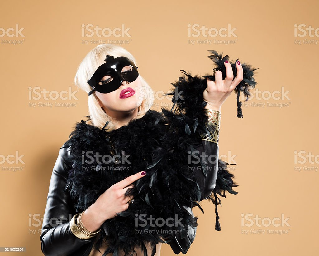 Sensual woman wearing costume - feather boa and face mask stock photo