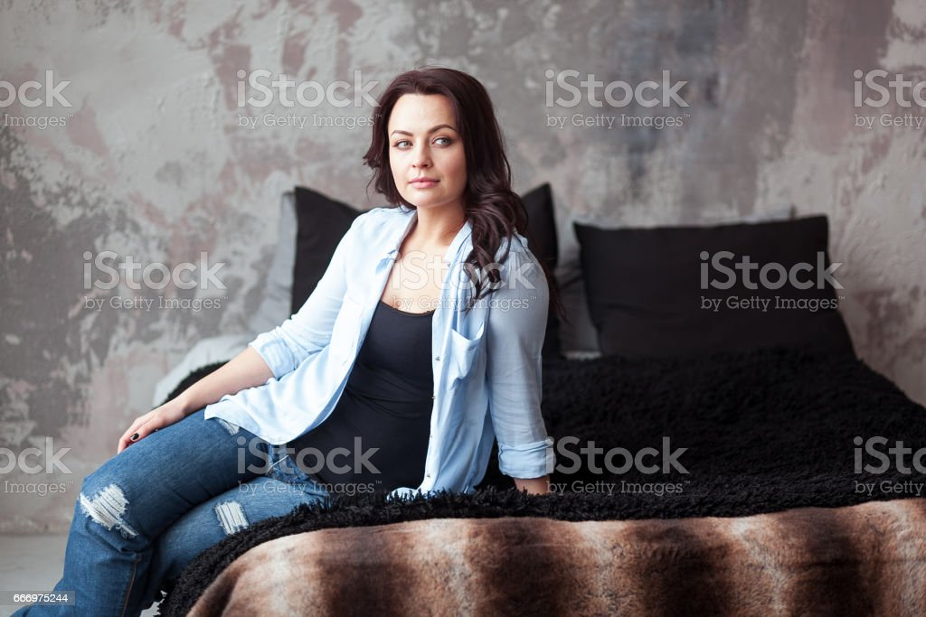 Sensual woman with dark hair in blue shirt and jeans sitting on a bed at home. Loft style interior stock photo