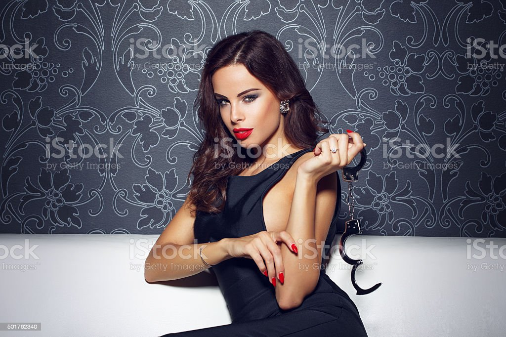 Sensual woman with red lips holding handcuffs stock photo