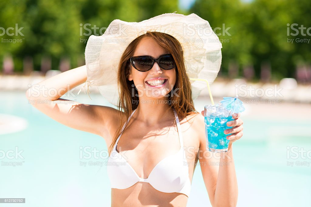 sensual woman with sunglasses drinking a cocktail stock photo