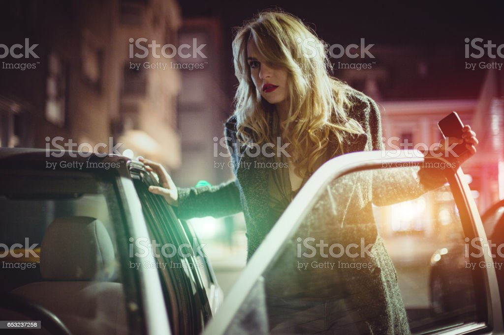Sensual young woman getting into car stock photo