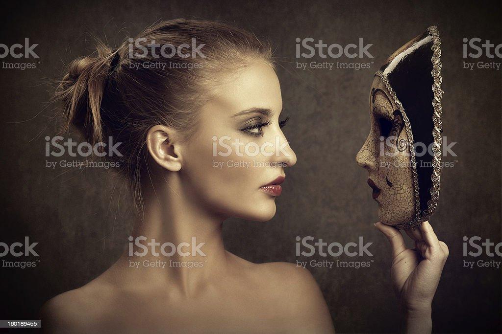 Sensual young woman looking at a venetian mask royalty-free stock photo