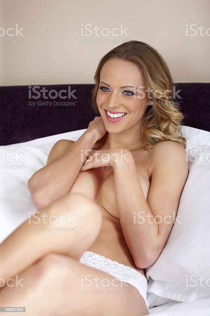Sensual young woman lying on bed covering her breasts royalty-free stock photo