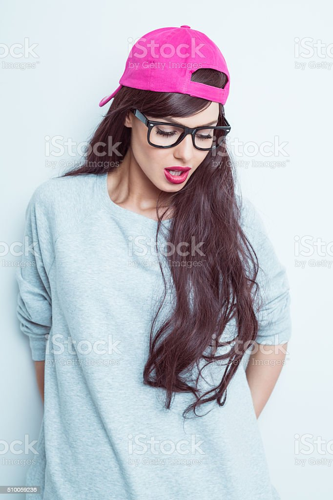 Sensual young woman wearing nerd glasses and pink baseball cap stock photo