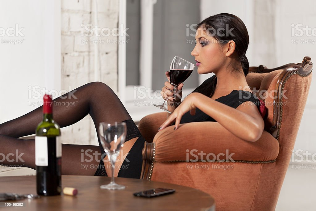 Sensually dressed woman sipping wine, waiting for partner royalty-free stock photo
