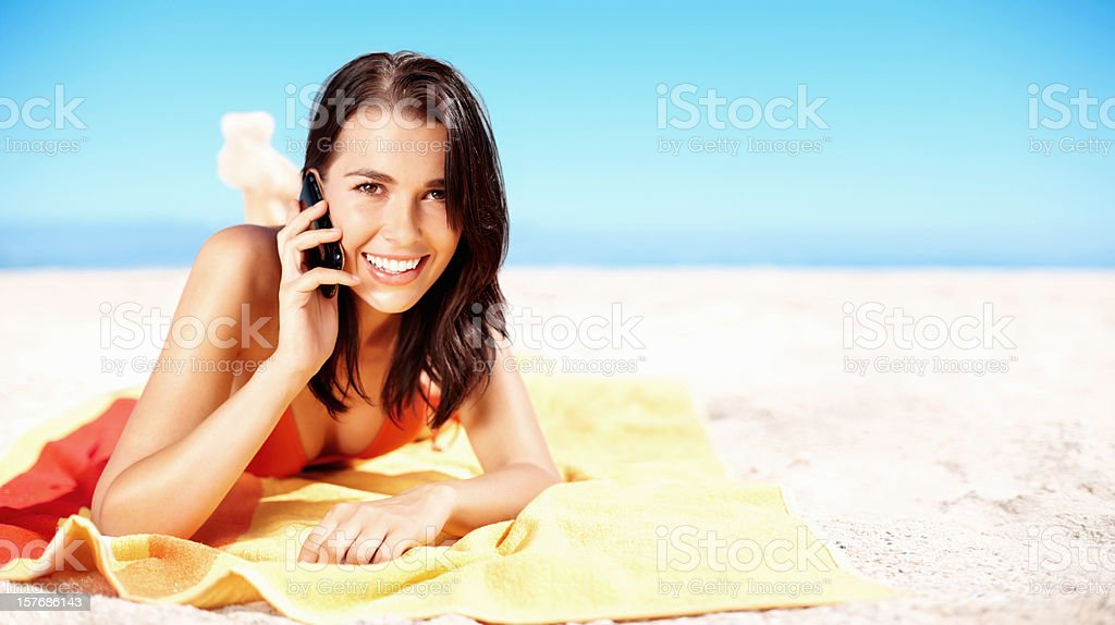 Sensuous young girl over the cell phone on beach, copyspace royalty-free stock photo