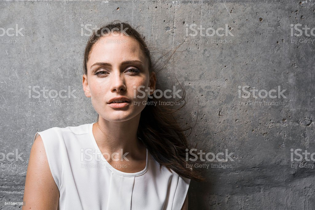 Sensuous young woman against wall stock photo