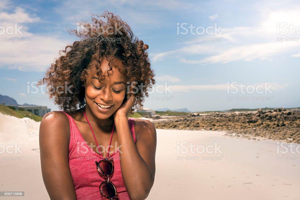 Sensuous young woman enjoying wind at beach stock photo