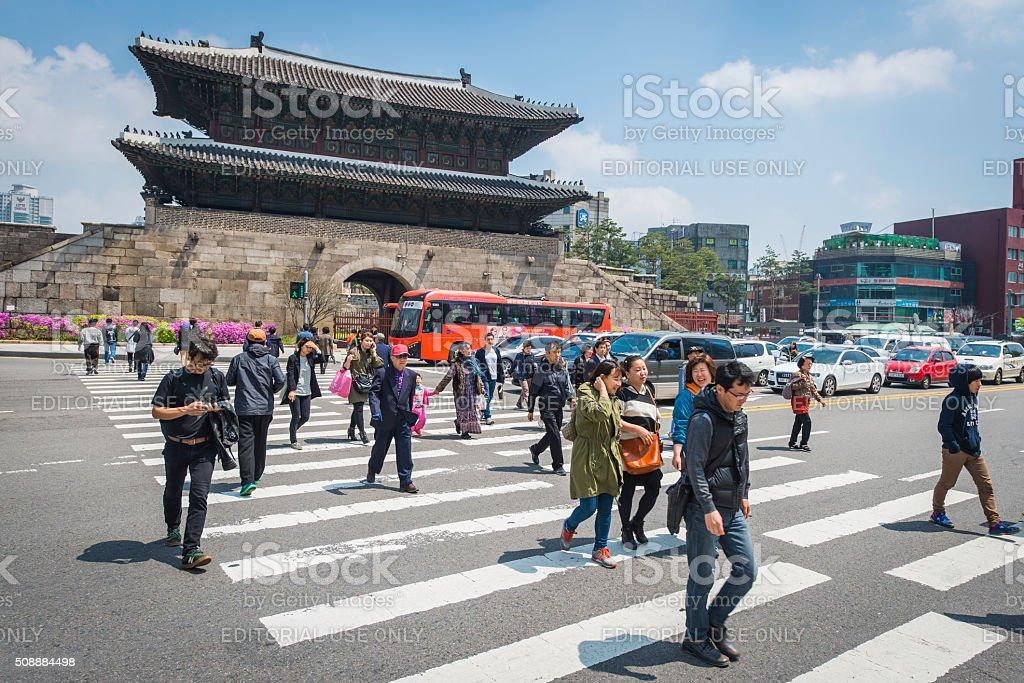Seoul pedestrians crossing through traffic Heunginjimun Dongdaemun Gate South Korea stock photo