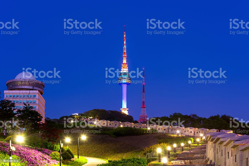 N Seoul Tower with full moon Located on Namsan Mountain. stock photo