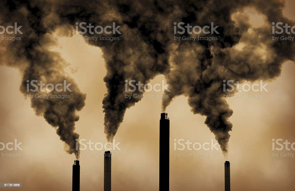 Sepia image of smoke coming from tall industrial chimneys stock photo