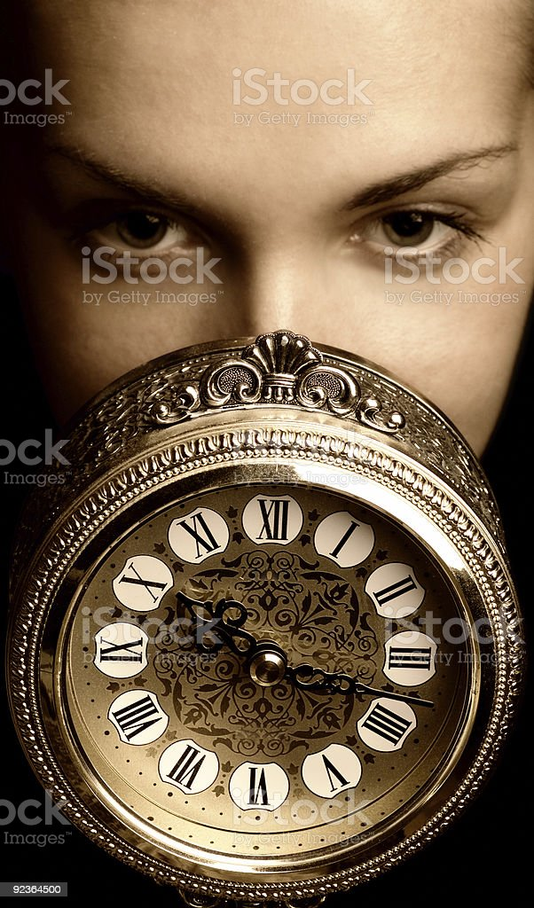 Sepia picture of a girl's face with clock royalty-free stock photo