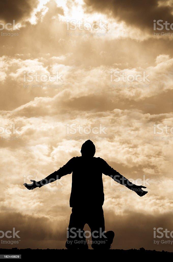 Sepia silhouette of man praying towards the sky on his knees royalty-free stock photo