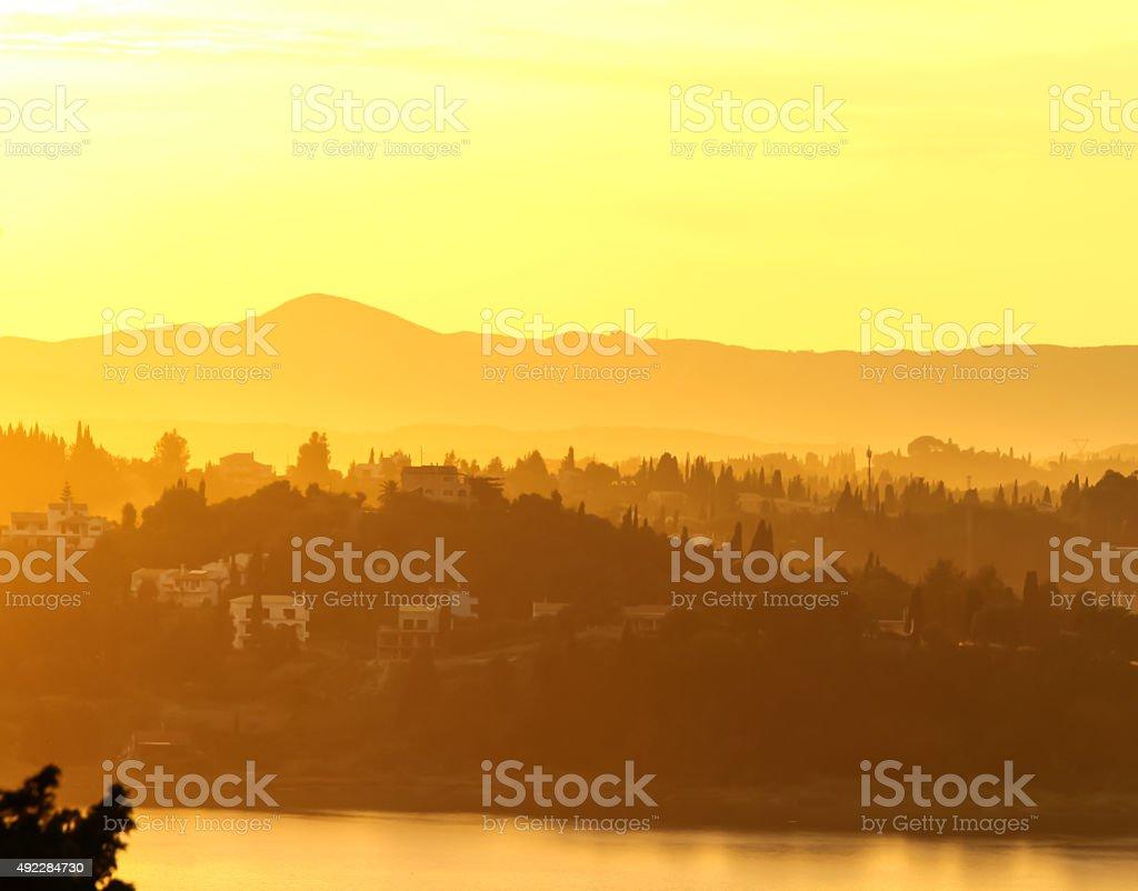 Sepia sunrise in the foggy haze, Corfu, Greece stock photo