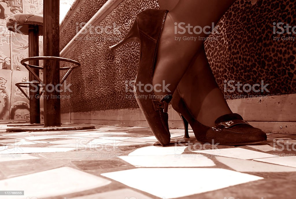Sepia tone close up of a woman's feet in high heels at a bar royalty-free stock photo