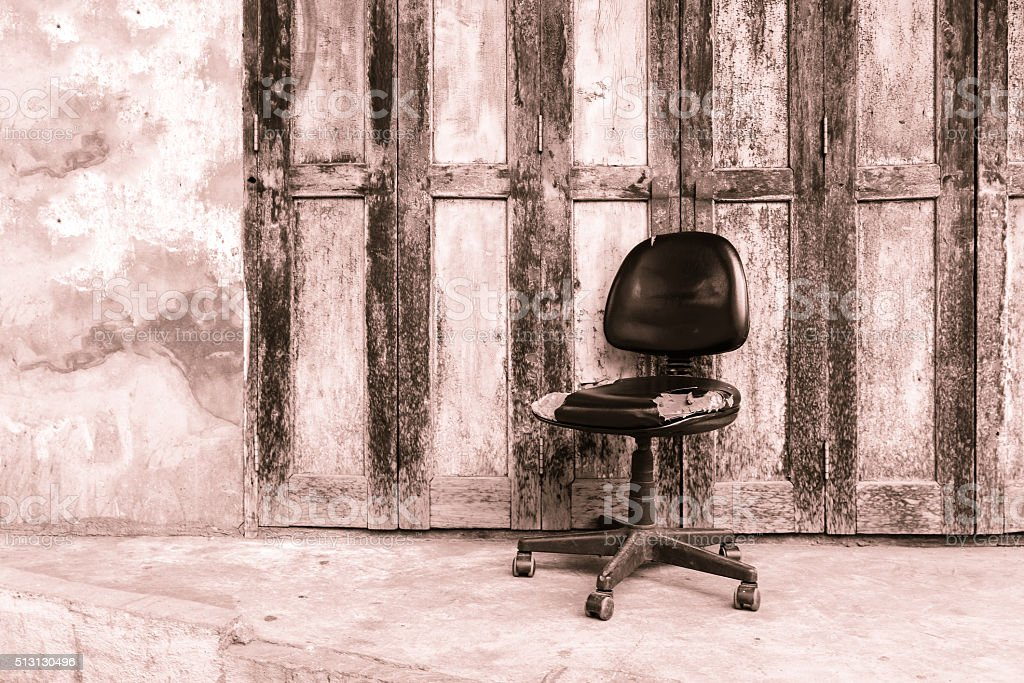 Sepia tone of Lacked seat with vintage wooden door background. stock photo