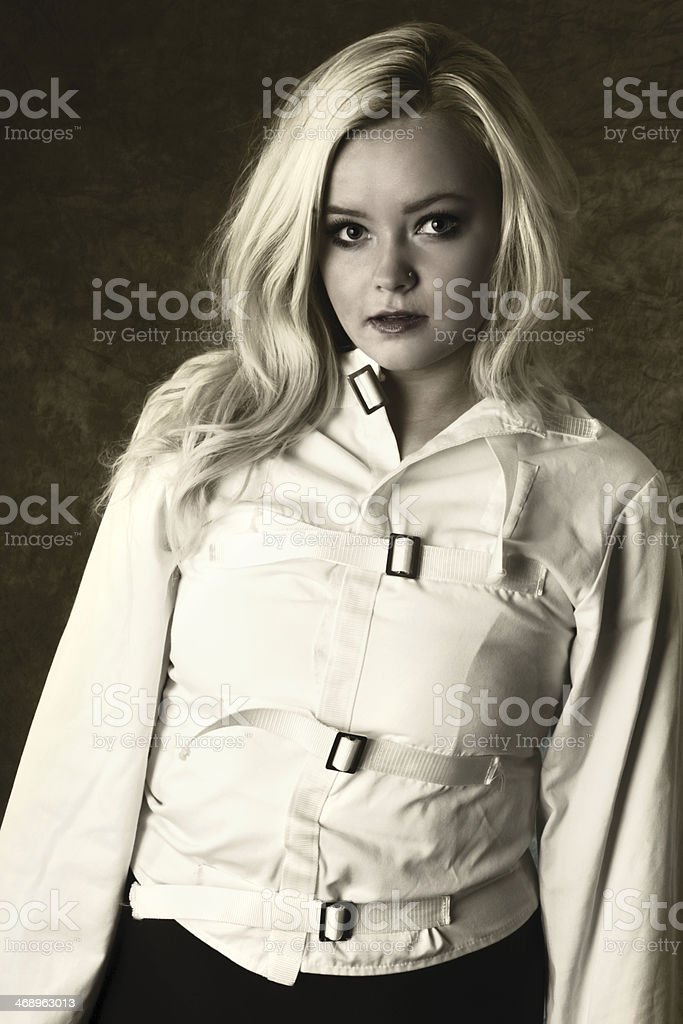Sepia toned image of blonde teen in straitjacket. royalty-free stock photo
