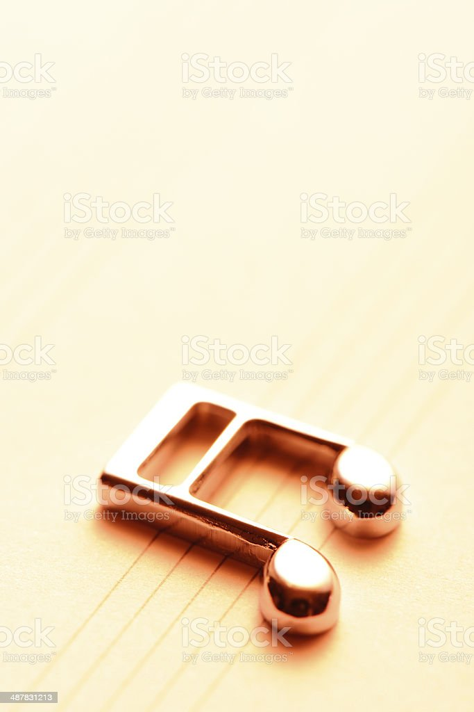 Sepia toned image of metal musical note with sheet music royalty-free stock photo