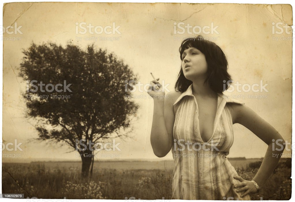 Sepia Toned Image of Young Woman Smoking by Tree stock photo
