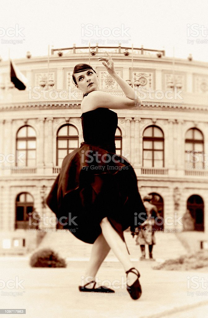 Sepia Toned Portrait of Ballerina Dancing Against Old Building royalty-free stock photo