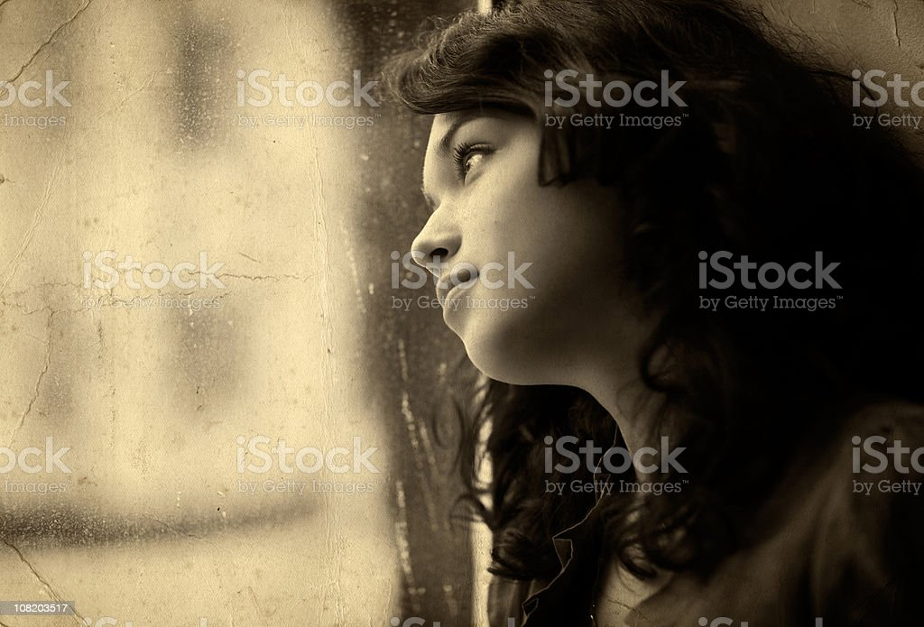 Sepia Toned Portrait of Pensive Young Woman Looking Out Window stock photo