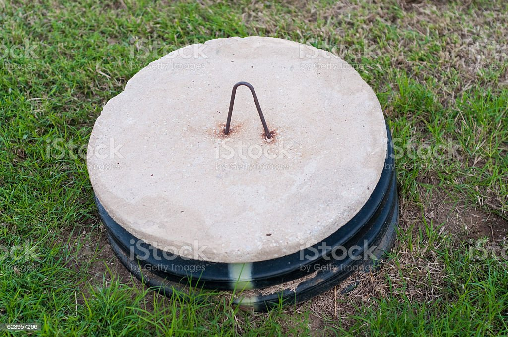 Septic tank lid in the middle of a yard. stock photo