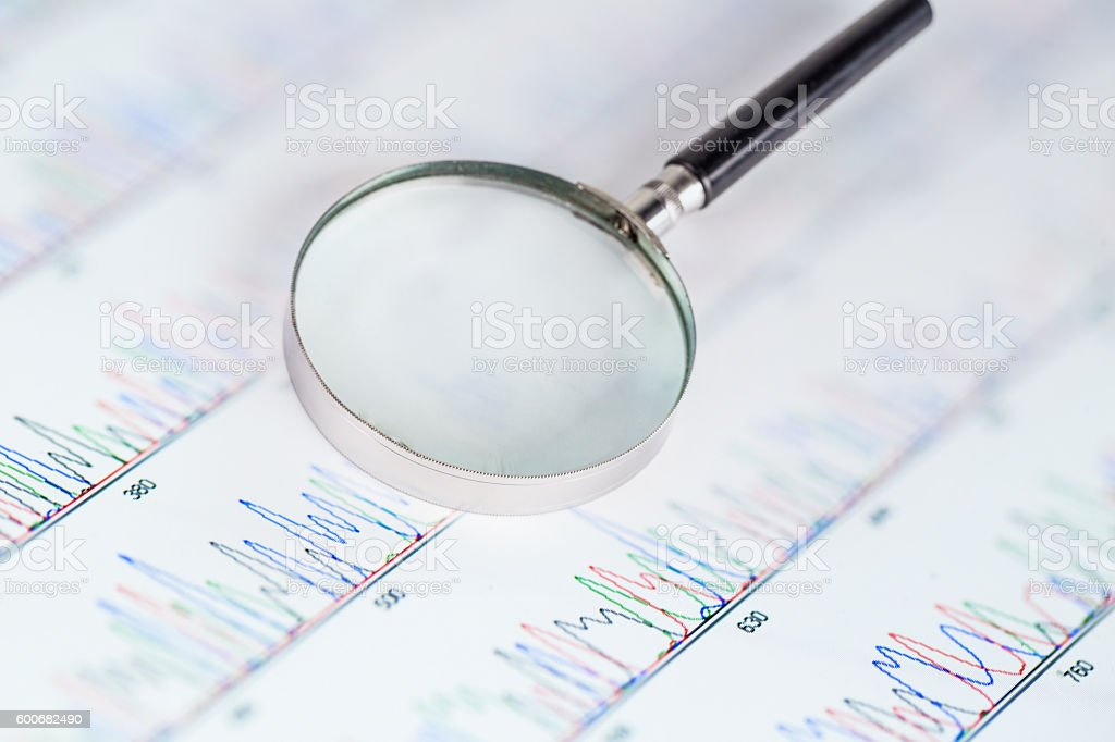 DNA sequencing peaks show on tablet with magnifier stock photo