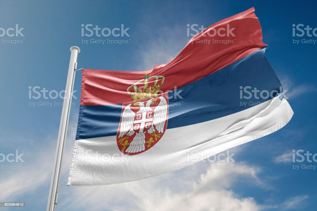 Serbia Flag is Waving Against Blue Sky stock photo
