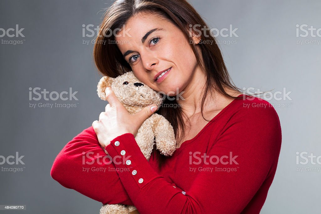 serene 30s girl using symbol of childhood for baby announcement stock photo