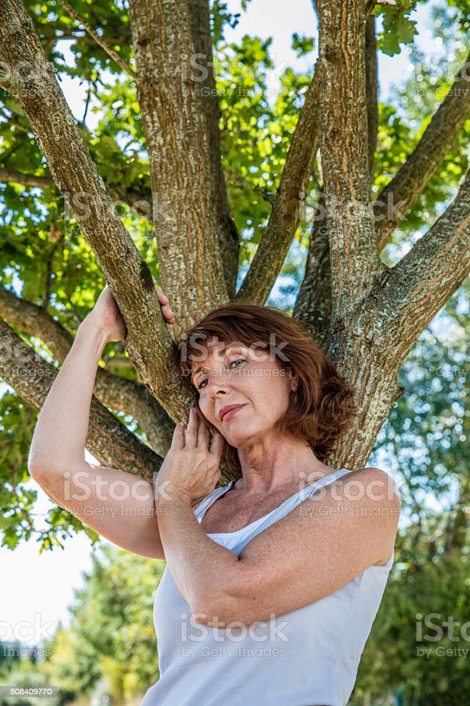 serene 50s woman under tree for strength and family roots stock photo