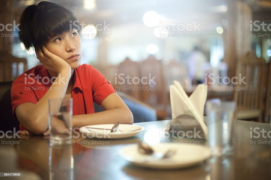 Serene Asian girl in restaurant thinking while waiting for food. stock photo