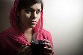Serene beautiful Indian woman with coffee mug at home.
