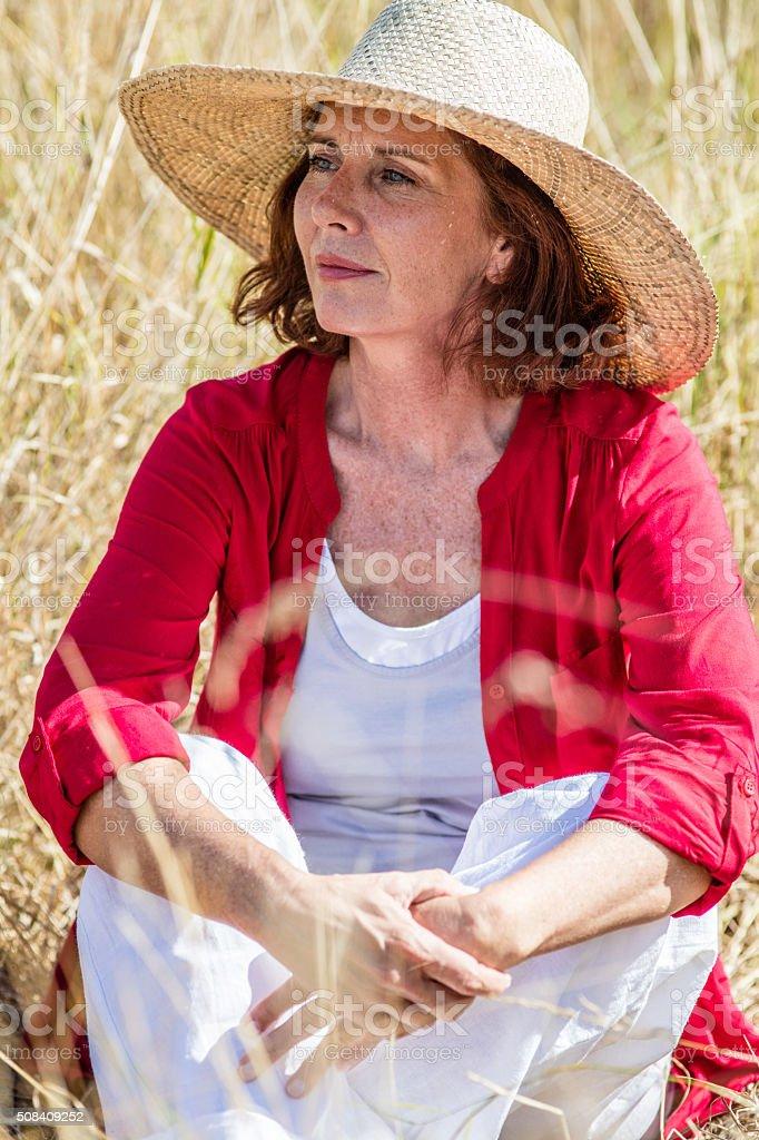 serene beautiful lady enjoying summer under straw hat stock photo
