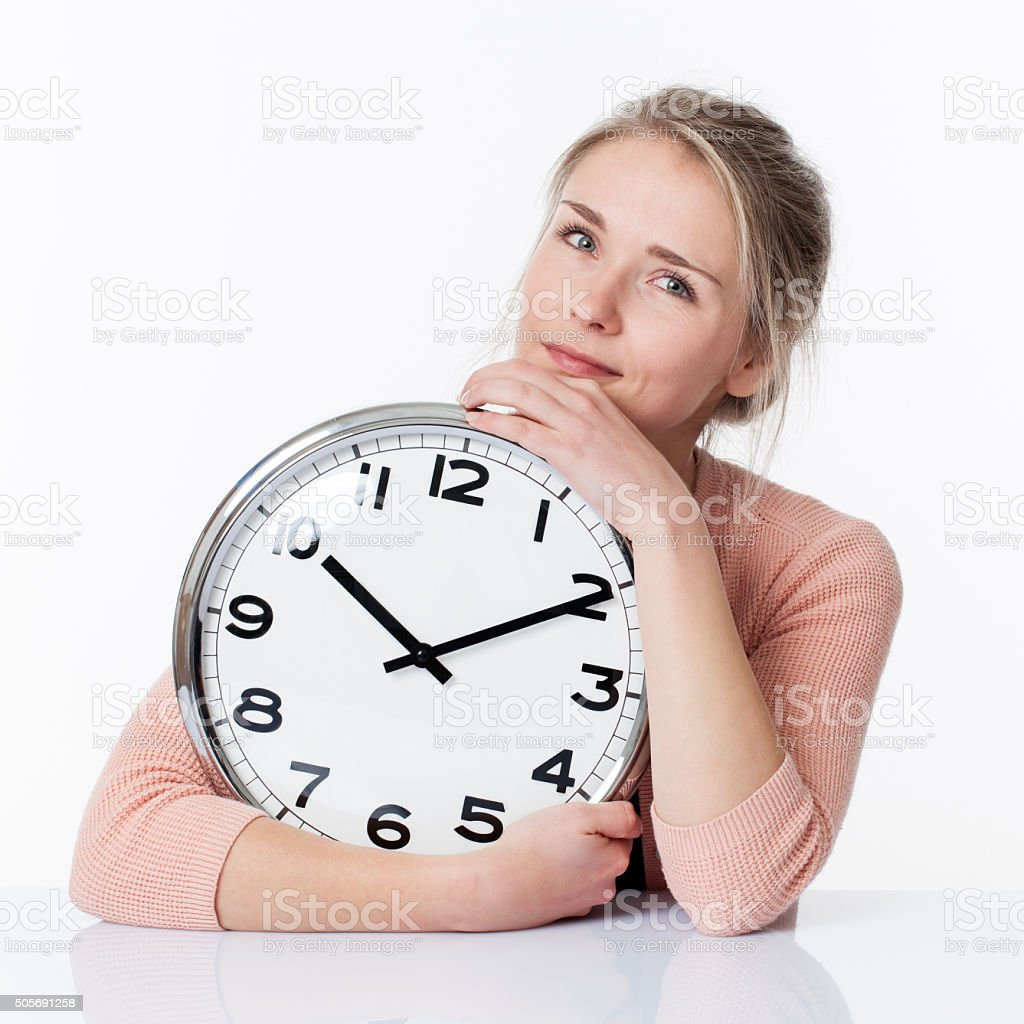 serene beautiful young blond woman embracing a clock stock photo