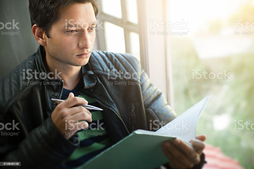 Serene, college student sitting near window with book pen. stock photo