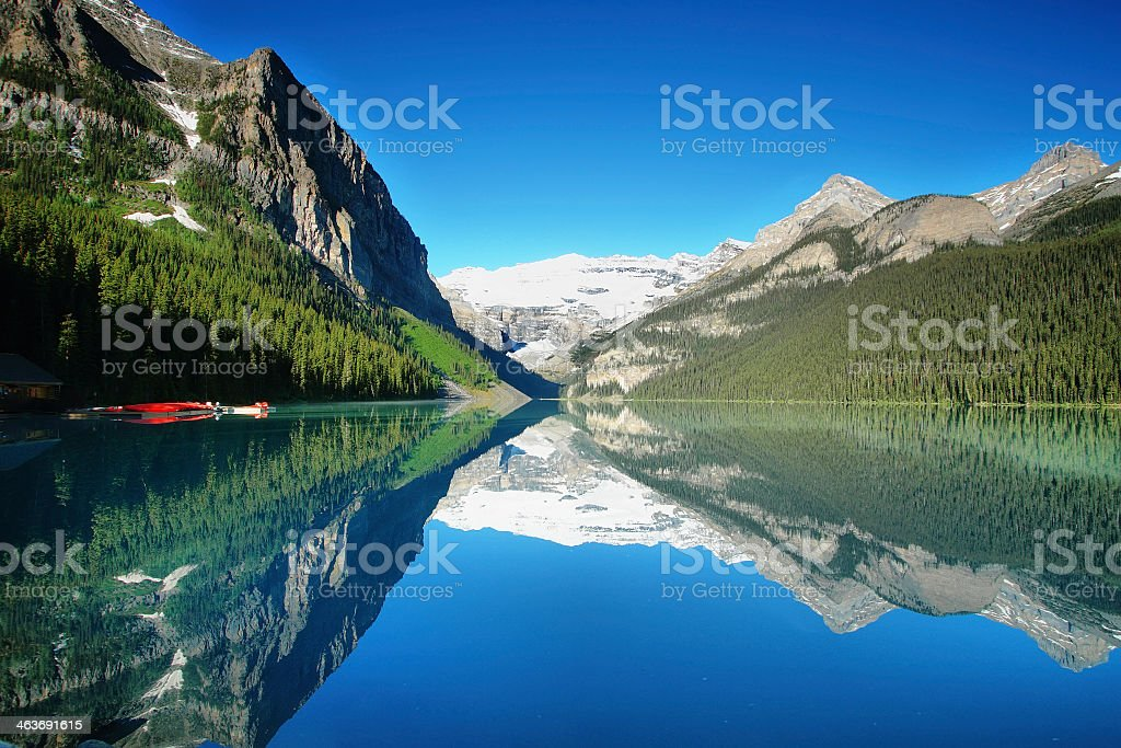 Serene Lake Louise surrounded by greenery in Alberta, Canada stock photo