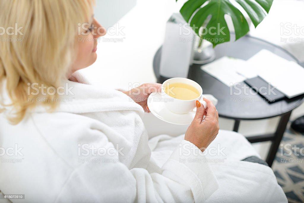 Serene mature lady enjoying healthy drink stock photo