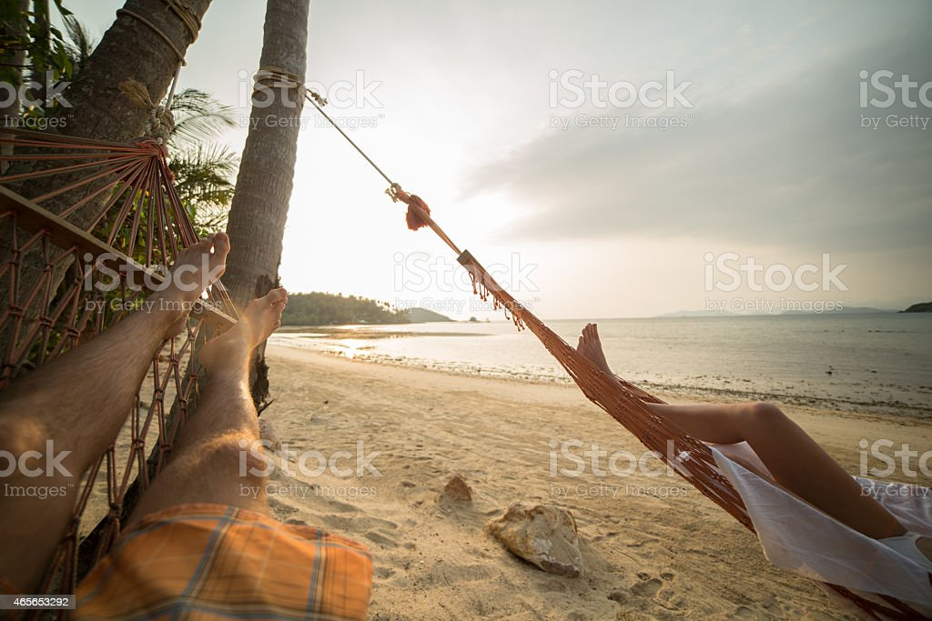 Serene people relaxing on hammock at sunset on tropical beach stock photo