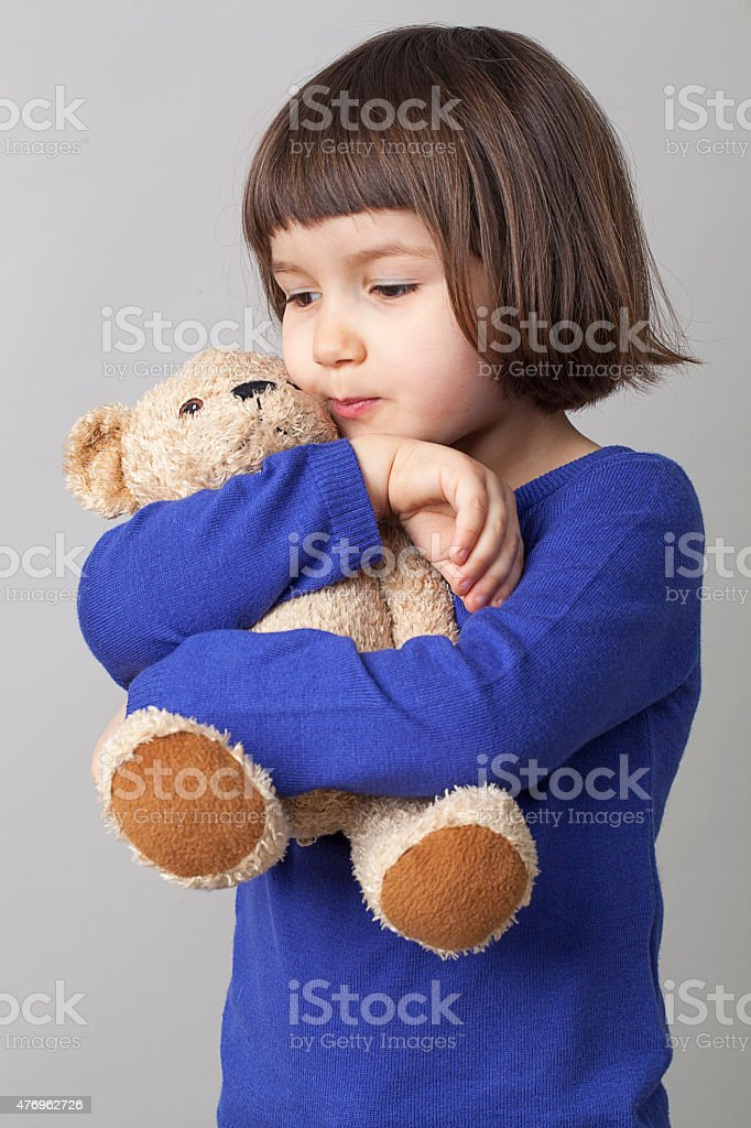 serene preschool girl hugging her teddy bear with tenderness stock photo