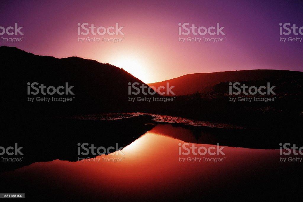 Serene scene of sun's last rays reflected in calm water stock photo