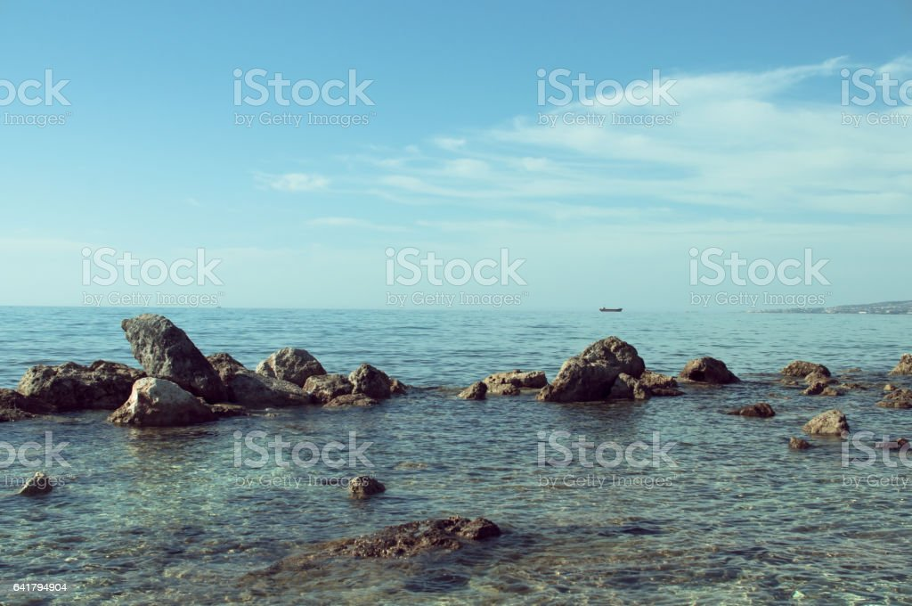 Serene seascape with rocks in foreground and boat on horizon stock photo