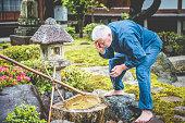 Serene Senior Caucasian Man in Buddhist Temple Garden, Kyoto, Japan
