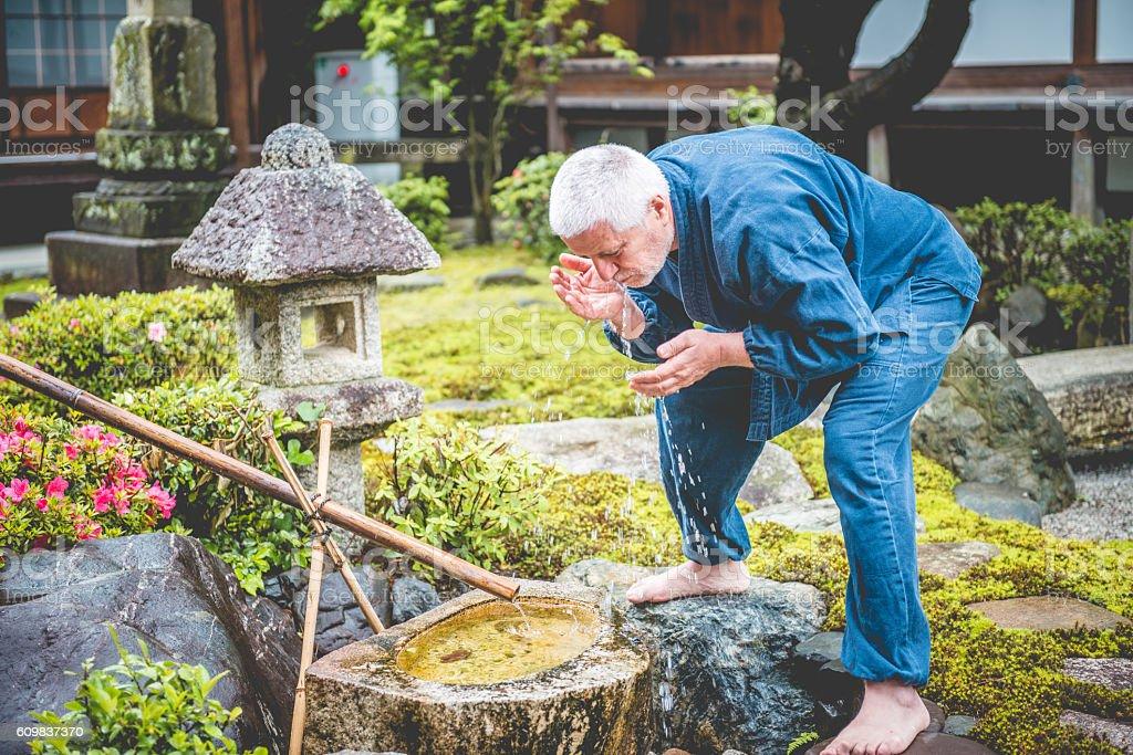 Serene Senior Caucasian Man in Buddhist Temple Garden, Kyoto, Japan stock photo