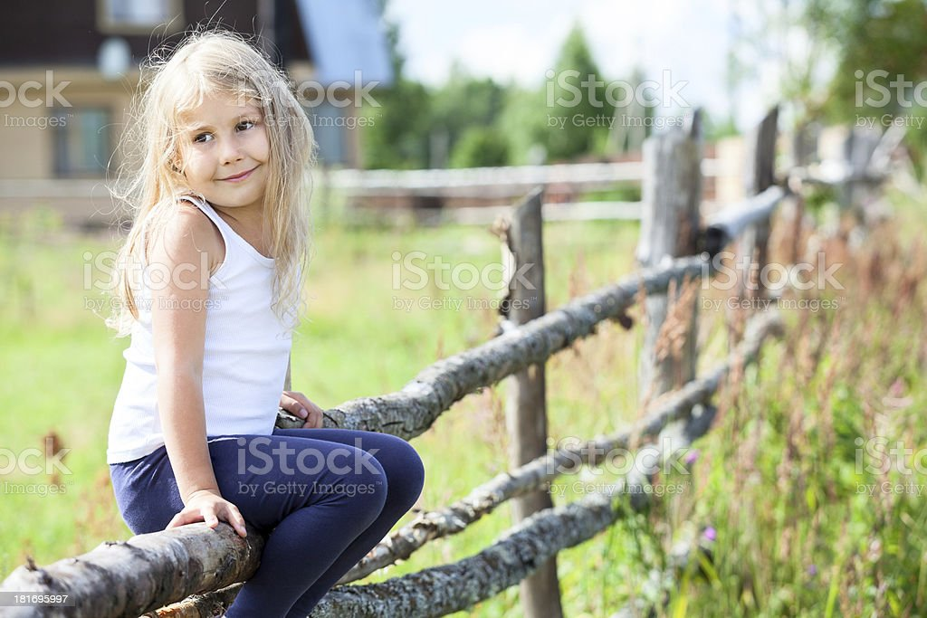 Serene smiling child sitting on log of fence royalty-free stock photo