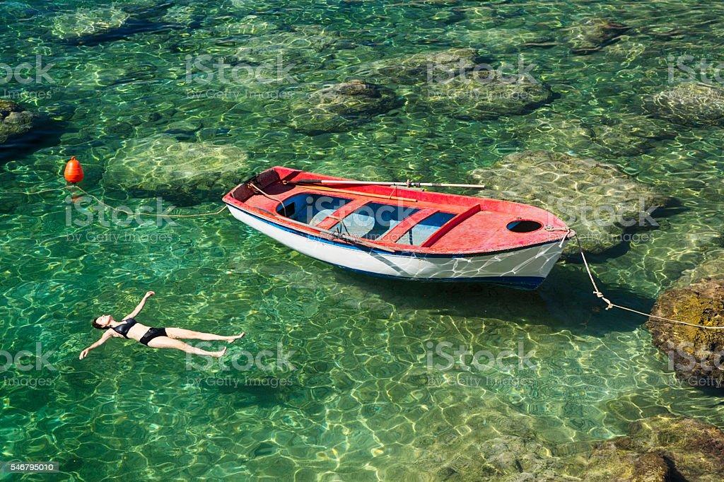 Serene Woman Floating on Clear Aegean Sea in Greece stock photo