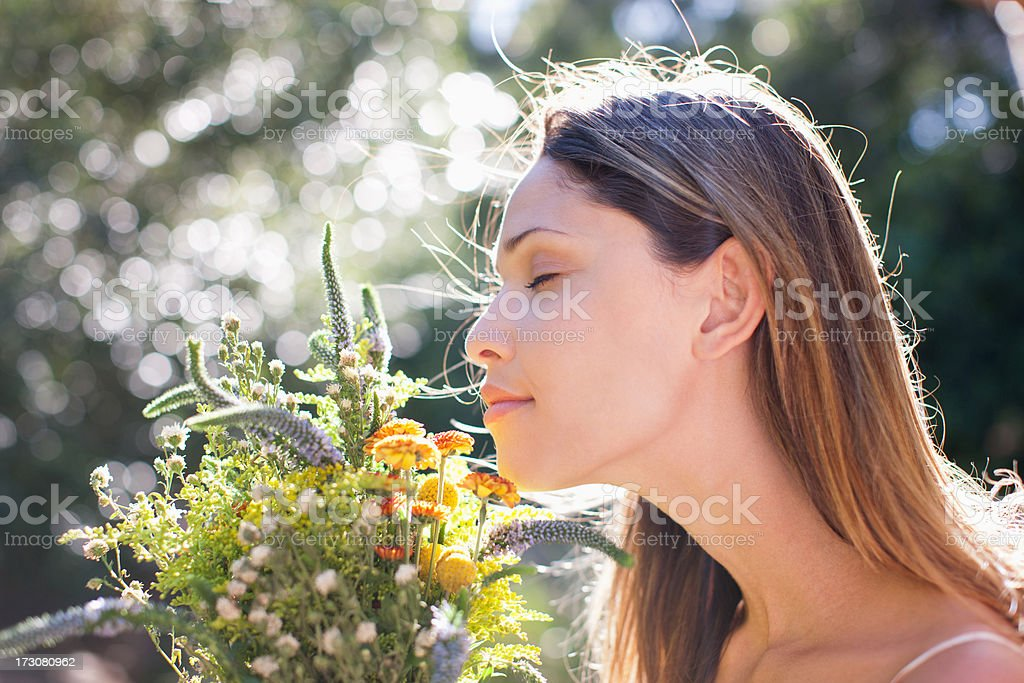 Serene woman smelling bouquet stock photo