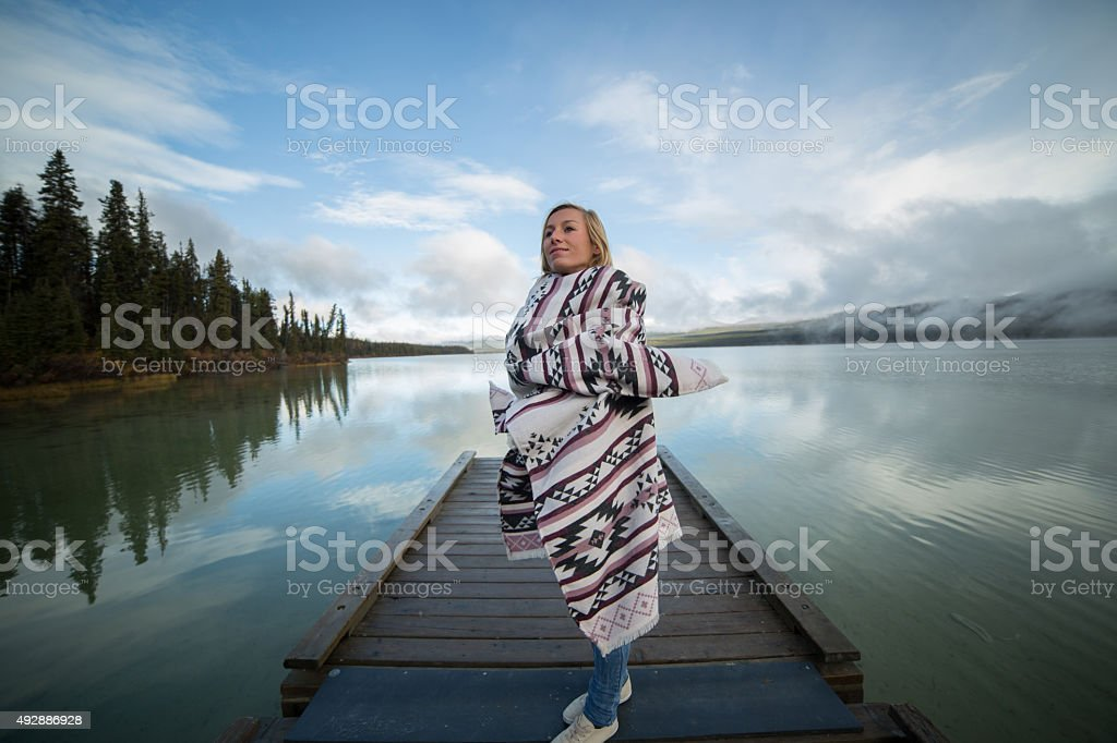 Serene woman stands on pier relaxing by the lake stock photo